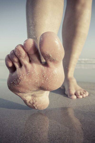 Planta del pie de persona andando por la playa
